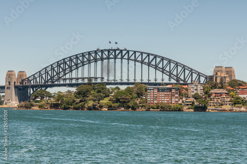 Sydney, Australia - December 11, 2009: Harbour Bridge, full metal span, bow and stone anchor towers against blue sky and above East shore with green vegetation and buildings. Azure bay in front.