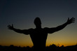 Silhouette of muscular man posing shows his muscles against the sky at sunset. Fitness and sport lifestyle concept.
