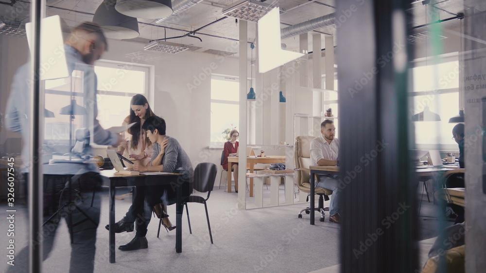 Fototapeta Multiethnic team working in modern trendy office. Happy young smiling creative millennials work in light coworking 4K.