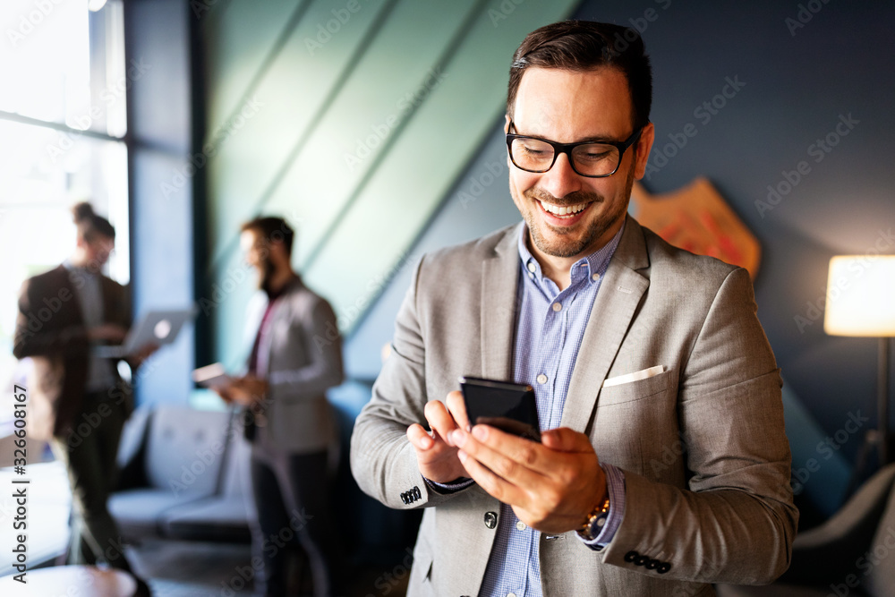 Fototapeta Handsome businessman checking emails on the phone in modern office