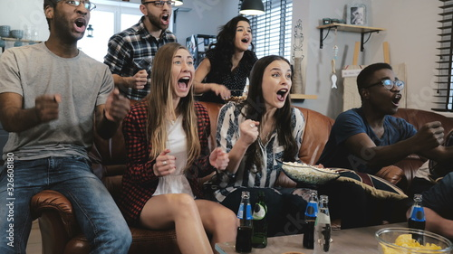 Fototapeta African American sports fans celebrate win at home. Passionate supporters shout watching game on TV. 4K slow motion. obraz