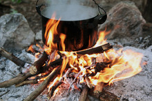 A Pot Of Water Boiling Over A Fire And A Flame. Preparing Food On Campfire In Wild Camping