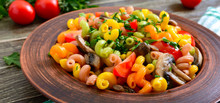 Tasty Warm Salad. Colored Pasta With Mushrooms And Fresh Tomatoes In A Bowl On A Wooden Table. Pasta Colorata.
