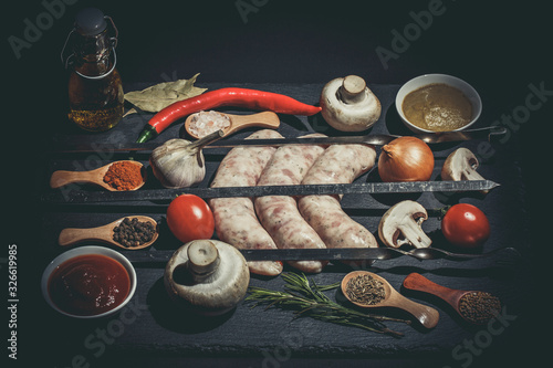 Photo Raw sausages with skewers, different vegetables, spices and ingredients on a bla
