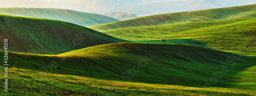 hilly field. tourist in a picturesque field. rural landscape Wallpaper Mural
