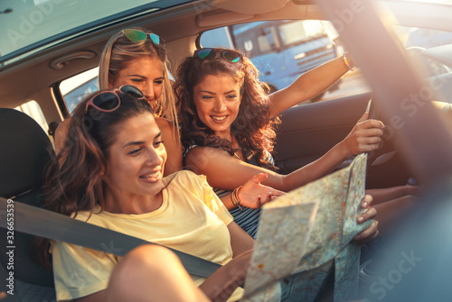 Obraz Three female friends enjoying road trip traveling at vacation in the car. - fototapety do salonu