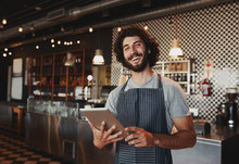 Handsome Young Caucasian Coffee Shop Owner Wearing Apron Laughing Using Digital Tablet