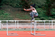 African-American Athlete Sprinter Jumping A Hurdle