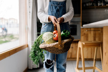 Woman Holding A Basket Of Vege...