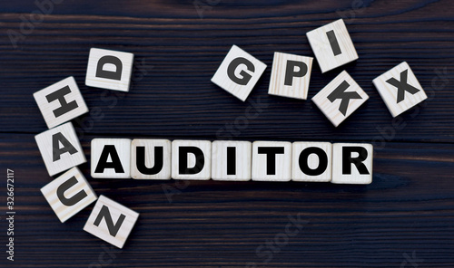 Photo Concept word auditor on cubes on a dark wooden background