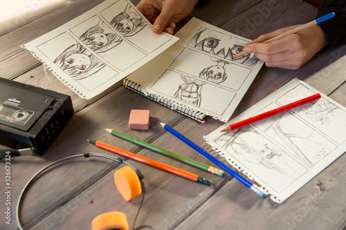 Artist drawing an anime comic book in a studio. Wooden desk, natural light - 326673324