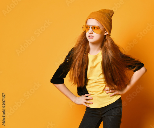 Photo Teen girl with red hair in hat, stylish glasses and yellow t-shirt is posing wit