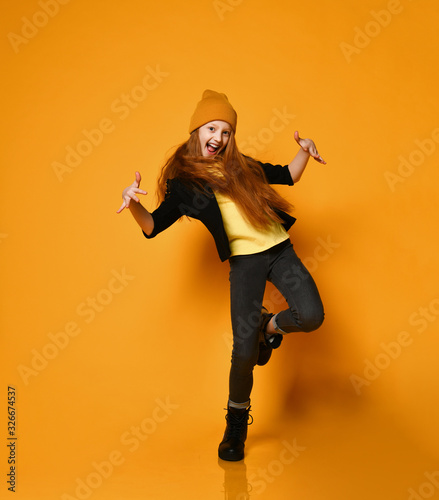 Canvastavla Cheerful teen girl with long red hair in knitted hat, yellow glasses and t-shirt