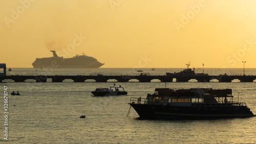 Photo Barcos e navio em silhueta no por do sol