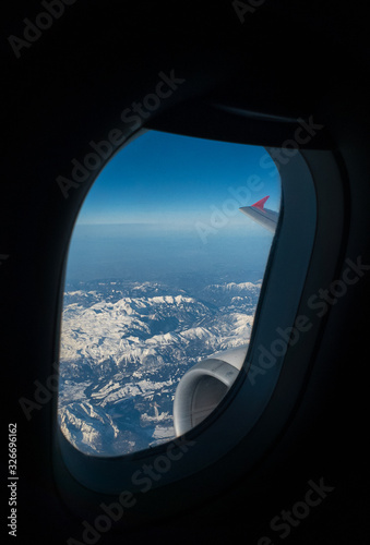 Mountains and fragment of the wing with turbofan engine and winglet seen through Wallpaper Mural