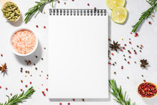 Assortment Of Spices And Herbs And Blank Notepad On White Kitchen Table. Recipe Book Template. Culinary Blog Social Media Concept.