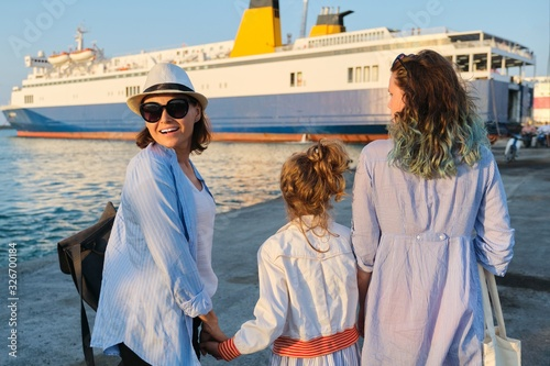 Sea family vacation, mother and daughters in the seaport looking at the ferry Fototapeta