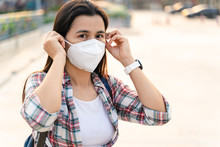 Asian Woman Wearing N95 Mask To Protect Pollution PM2.5 And Virus. COVID-19 Coronavirus And Air Pollution Pm2.5 Concept.