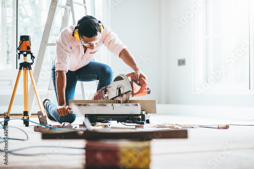Fotografía Smart indian contractor hand using sawing machine wood work and working overall equals a wooden bar in the house renovation background
