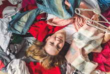 Fast Fashion, Girl Lies On A Bunch Of Colorful Clothes In The Dressing Room. Concept Of Recycling, Second Hand, Eco, Minimalism, Consumption Of Goods, Shopaholic