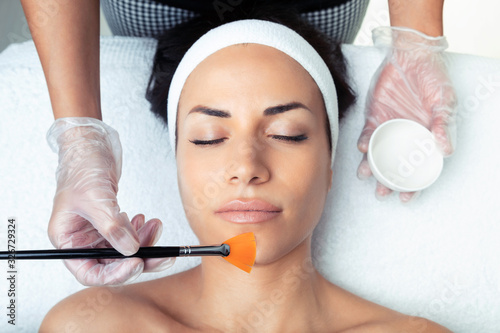 Fotografía Cosmetologist making a chemistry peeling for rejuvenating the face to woman on the spa center