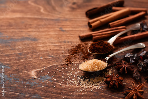 Assorted natural cinnamon, cane brown sugar, ground coffee, anise stars baking ingredients on a rustic brown background Wallpaper Mural