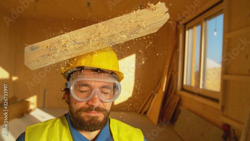 Fotografiet PORTRAIT, CLOSE UP: Wooden board falls on an unsuspecting builder's head