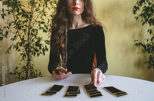 Photo beautiful young woman in a black velvet dress lays out cards on the table