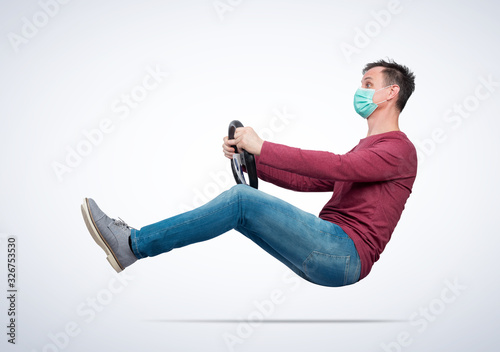 Fotografia Man in respiratory mask drives a car while holding a steering wheel