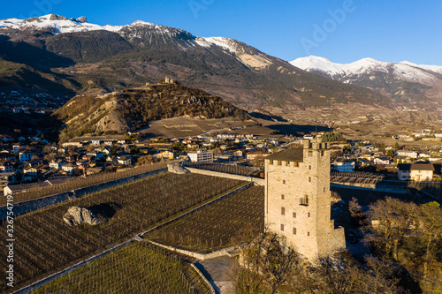 Fotografie, Obraz Medieval tower and a vineyard castle on the top of hill near the town of Sierre