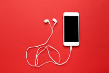 Earphones With Mobile Phone On Red Background
