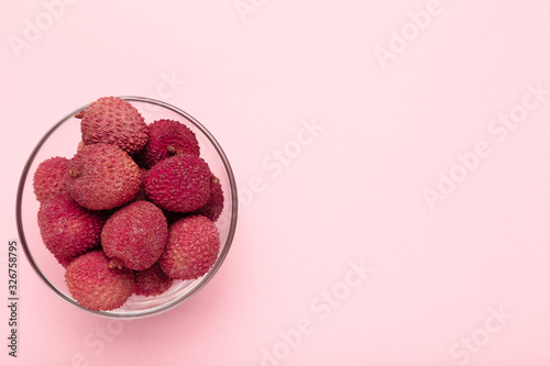 Tasty lychee in bowl on pink background