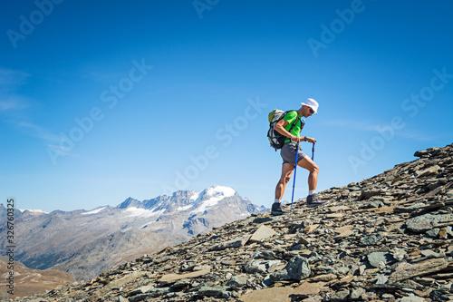 Fototapeta Man trekking in the Alps in a beautiful sunny day. Grand Paradiso National Park. Italy obraz