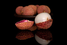 Lot Of Whole One Piece Of Fresh Lychee One Peeled With Brown Ceramic Coaster Isolated On Black Glass