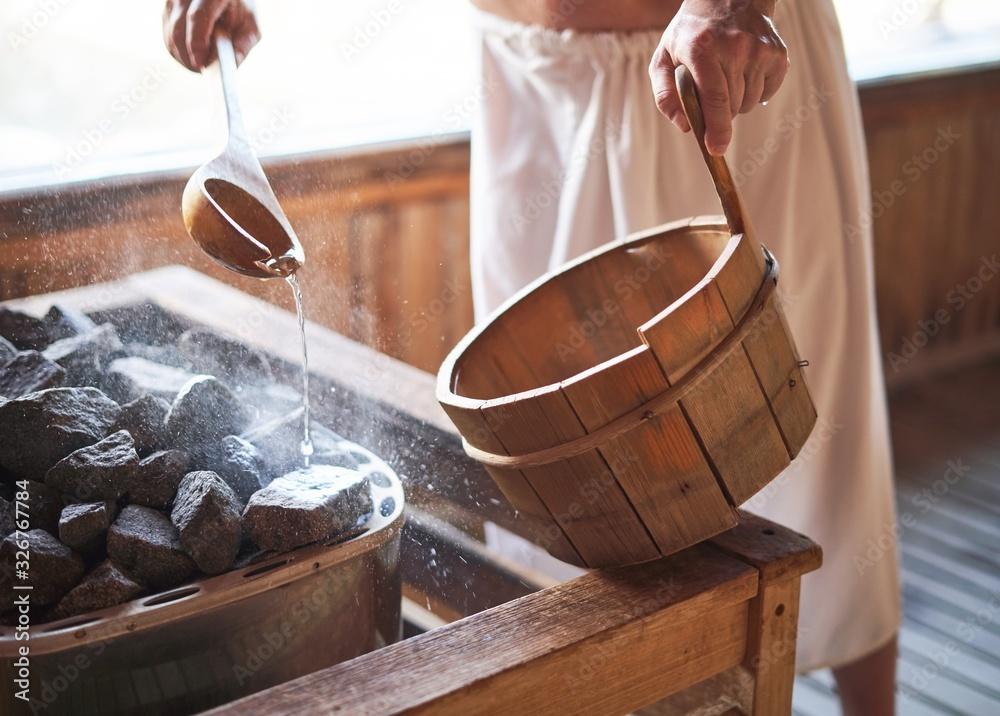 Fototapeta Man pouring water into hot stone in sauna room.