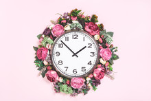 Part Of Big Analogue Plain Wall Clock In Full Bloom Flowers On Candy Pink Background. Close Up With Copy Space, Time Management Concept. Daylight Saving Time. Spring Or Wedding. Womens Day Picnic