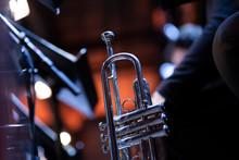 A Silver Plated Trumpet Resting On A Stand With A Stand Light In The Back During A Big Band Concert