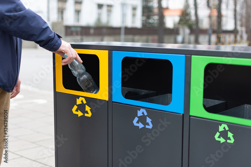 Hand of man throwing plactic bottle into trash bin for plastic waste Canvas-taulu