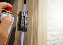 A Man Lubricates Door Hinges W...