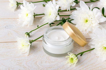 Obraz na płótnie Canvas Moisturizing face cream in an open glass jar with golden lid and white chrysanthemum flowers on a wooden table. Beauty, skincare and cosmetology concept.