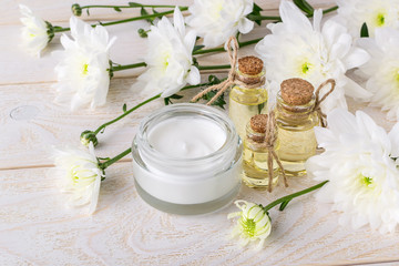 Obraz na płótnie Canvas Face cream in an open glass jar, three bottles of chrysanthemum essential oil and white chrysanthemum flowers on a wooden table. Beauty, skincare and cosmetology.