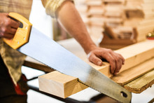 Worker Hands Use A Wood Cutter Or Saw On Wooden Board. Carpenter Work In Action.