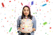 Young Female Celebrating Birthday And Blowing Candles On A Cake With Confetti Around