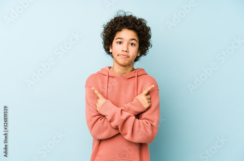 African american little boy isolated points sideways, is trying to choose between two options Canvas Print