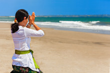 Young Balinese Woman Praying With Namaste Hands On Sea Beach At Ceremony Before Silence Day Nyepi. Religious Holidays, Traditional Festivals, Rituals, Art, Culture Of Indonesian People On Bali Island.