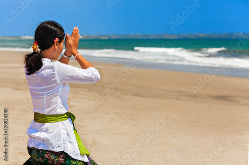 Leinwand Poster Young balinese woman praying with namaste hands on sea beach at ceremony before silence day Nyepi