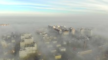 Aerial View At The Houses That Are Covered With Morning Fog. Flight Over The