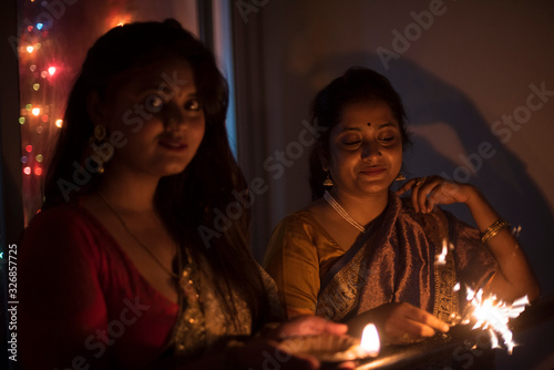 Fototapeta Two young and beautiful Indian Bengali women in Indian traditional dress are celebrating Diwali with diya/lamp and fire crackers on a balcony in darkness. Indian lifestyle and Diwali celebration obraz na płótnie