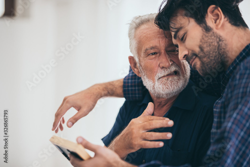 Fototapeta An adult hipster son and senior father at home, talking. obraz