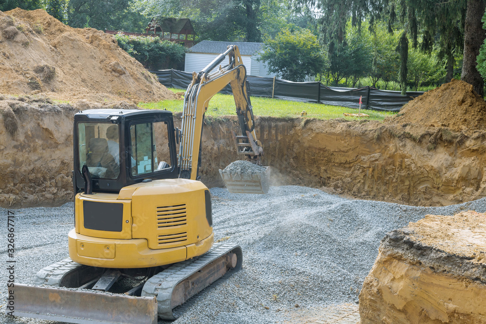 Fototapeta Excavator digging bucket scooping gravel from a building foundation